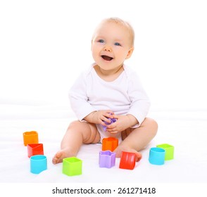 Funny baby sitting playing with colorful toys and laughing