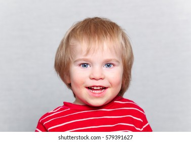 funny baby smile toddler blonde boy in red and white striped dress