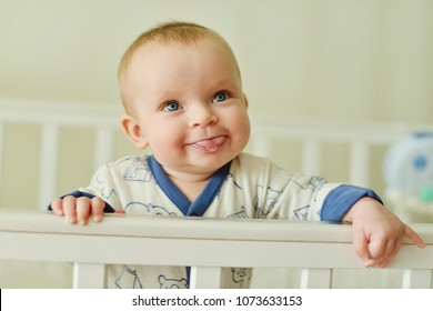funny baby standing in the bed and showing tongue