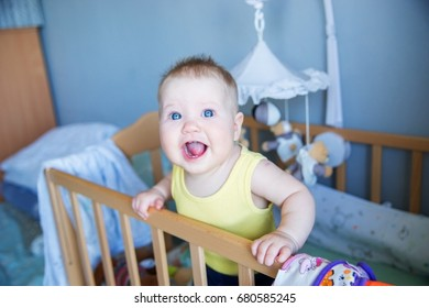 Funny baby standing up in her crib in the room.