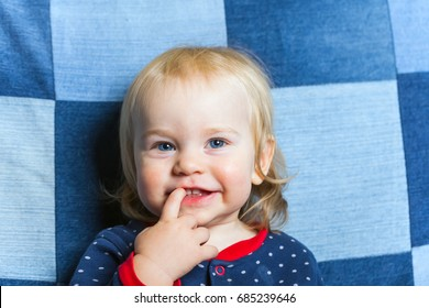 funny baby toddler blonde boy on a jeans background