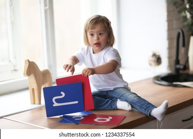 funny baby Toddler with Down syndrome learns and plays, real interior. Concept children with special needs and compensation and adaptation.