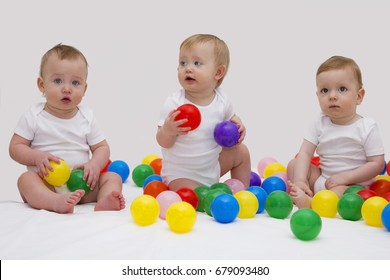 Funny baby triplets smiliing and playing with colorful balls. Studio shot.
