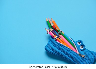 Funny Back to School concept - pencil case eating pencils on blue background. Space for text.