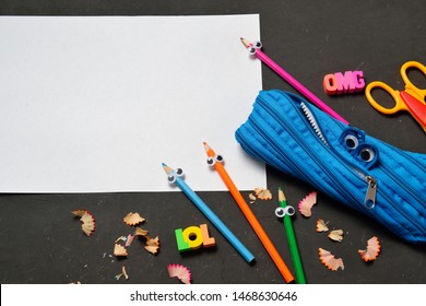 Funny Back to School concept - pencil case eating pencils on black chalk background. Space for text.