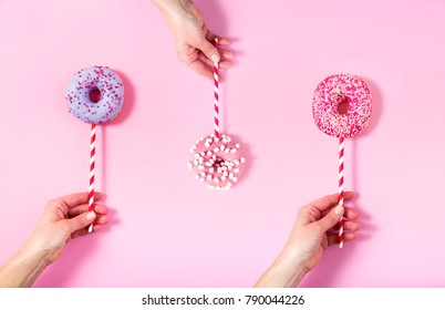 Funny bagel lollipops holding by hands. Sweetness happiness abstract conception.