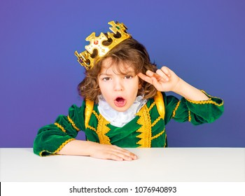 "A funny battle in a green royal, aristocratic outfit shows ""you are stupid or crazy"" sitting at a table on a lilac background."