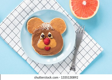 Funny Bear or Dog pancake food art for kids on bright blue background. Top view. Healthy breakfast children meal