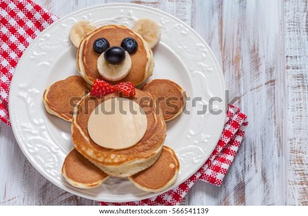 Des crêpes d'ours amusantes avec des baies pour le petit-déjeuner