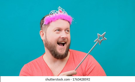 funny bearded freaky man in a pink T-shirt with a deadema on his head is dreaming with a magic wand in his hand. A funny wizard joke to make and fulfill a wish