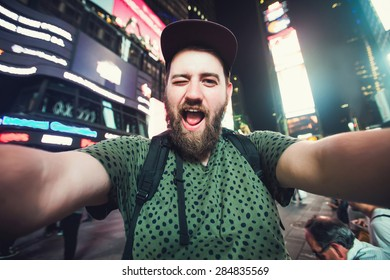 Funny bearded man backpacker smiling and taking selfie photo on Times Square in New York while travel alone across USA