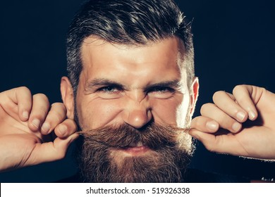 Funny bearded man with beard and gray hair stylish hipster male twirls moustache on dark background