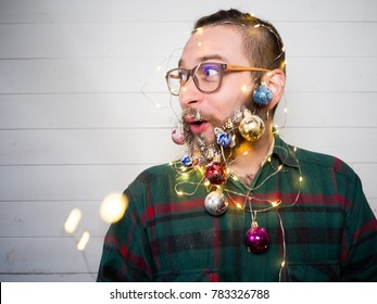 Funny bearded man in a New Year's image with snow and decorations on his beard