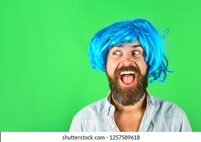 Funny bearded man wearing blue wig. Handsome bearded man with stylish mustache in wig. Fashion, art and creativity concept. Barbershop. Hipster in periwig. Happy stylish man in blue hair. Copy space.