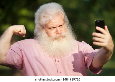 Funny bearded senior man with severe look demonstrating his muscles and biceps and taking selfie on smartphone, standing against blur green natural background in city park at sunny day.