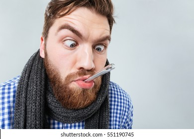 Funny bearded young man in scarf with thermometer in his mouth
