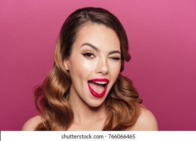 Funny beautiful brunette lady winking and smiling isolated while looking camera isolated