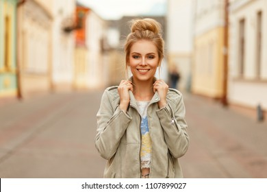 Funny beautiful happy woman smiling. Stylish model woman with a smile in a fashion jacket on the street