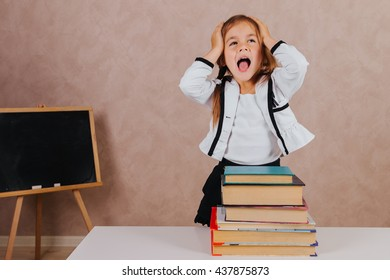 Funny and beautiful little cute schoolgirl in the classroom with books at the desk with emotions