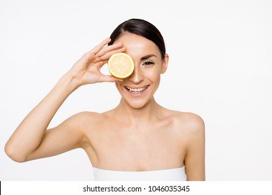 Funny beautiful smiling woman with halfs of lemon in hands