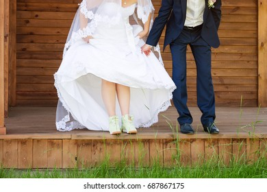 Funny beautiful wedding couple. Bride wearing green running shoes. Runaway bride, close up