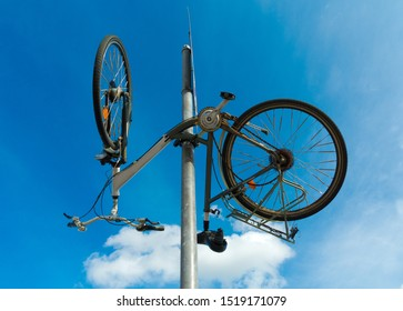 funny bicycle hanging upside down from a traffic sign