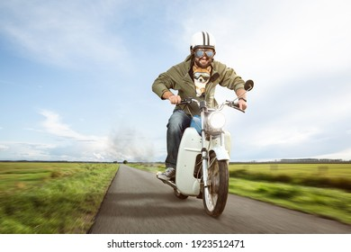 Funny biker riding a moped with his dog