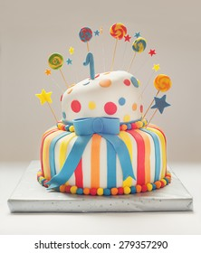Funny birthday cake with number one on top, sweet colorful decoration.