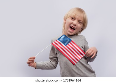 Funny blond boy holding an American flag on white background. Travel to USA with children.