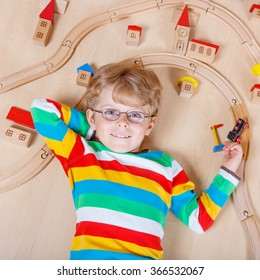 Funny blond child in glasses playing wooden trains and roalroad indoor. Active kid boy wearing colorful shirt and having fun with building and creating.