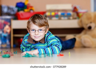 Funny blond child playing with lots of small toy soldiers, indoor. Active kid boy with glasses wearing colorful shirt and having fun at home or at nursery.