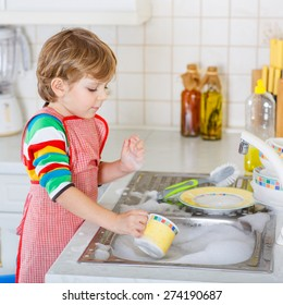 Funny blond kid boy washing dishes in domestic kitchen. Child having fun with helping his parents with housework. Indoors, kid in colorful clothes.