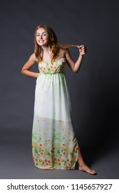 Funny blond natural girl holding her hair in her hand in a long flower dress on barefoot