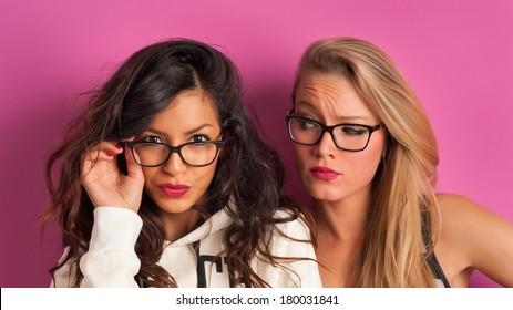 Funny blonde and brunette women portrait against pink background.