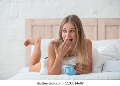 funny blonde with a cup of coffee yawning in bed