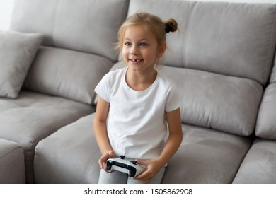 funny blonde girl without a tooth plays video games in a white t-shirt at home sitting on a gray sofa