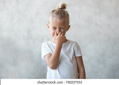 Funny blonde little boy with hair bun pinching nose and grimacing because of bad smell of dirty socks, toilet or armpits. Cute male child can't stand stink, posing isolated at grey studio wall