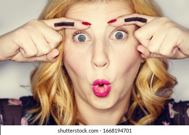 Funny blonde playfully makes eyebrows shape with her fingers. Smiling woman fool around. Facial expression, joke or fools day. Eyebrow master. Closeup girl face