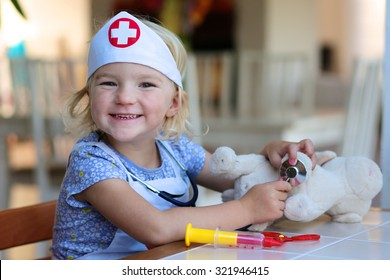 Funny blonde toddler girl playing doctor role game examinating her puppy using stethoscope sitting at small white table in playroom at home, school or kindergarten