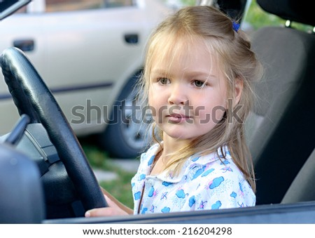 Funny Blonde Toddler Girl Sitting Of The Car On Driver Seat Holding Steering Wheel