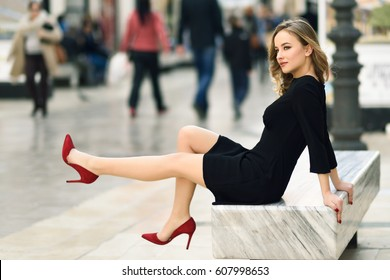 Funny blonde woman with beautiful legs in urban background. Beautiful young girl wearing black elegant dress, red high heels sitting on a bench in the street. Pretty female with long wavy hairstyle.