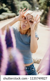 Funny blonde woman making faces with her hands over her face
