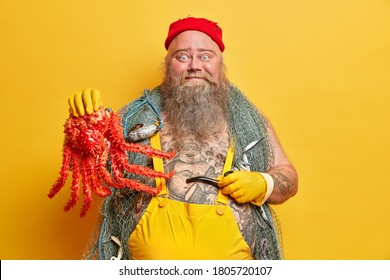Funny blue eyed seaman holds big octopus and smoking pipe, leads seafaring life, dressed in sailor clothes, poses against vivid yellow background, spends long period at sea. Sailing, boating