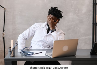 Funny bored at work african american doctor worker falling asleep at office desk, employee sleeping at workplace near laptop feel overworked concept