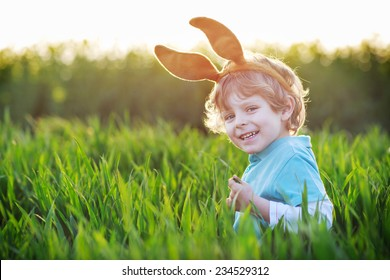 Funny boy of 3 years with Easter bunny ears playing in green grass on sunny spring day, celebrating Easter holiday