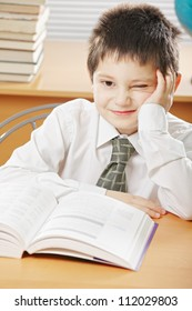 Funny boy with book sitting at desk