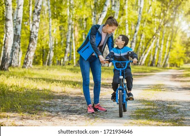 Funny boy cyclist learning to ride a bike with mom in the sunny forest on a bike. Adventure travel.