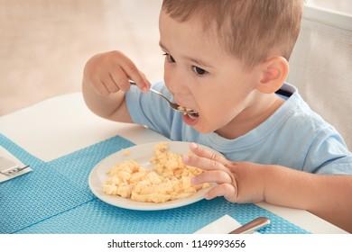 funny boy has Breakfast eggs alone holding a spoon