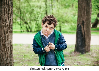 Funny boy having fun. The child makes faces outdoors