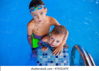 Funny boy and his cute baby smiling  brother  in swimming pool